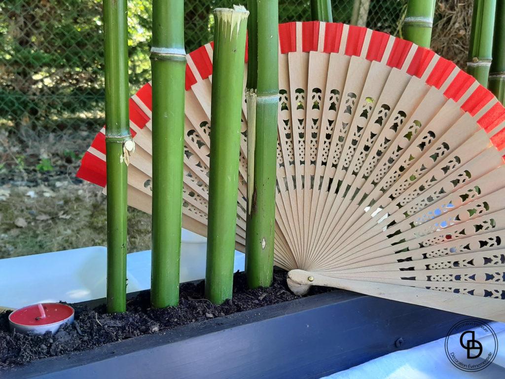 Détail de la décoration de table asiatique avec du bambou et un éventail rouge